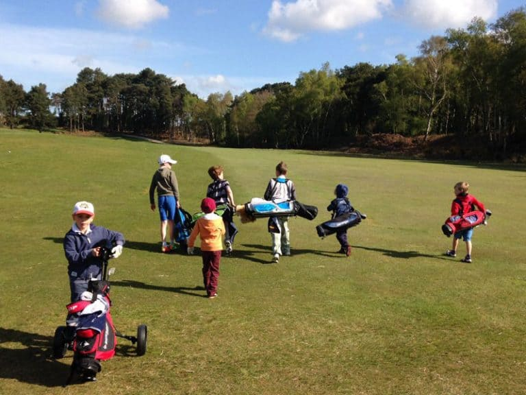 image of seven young golfers walking up the fairway as part of a group coaching session run by kelly bridges golf in dorset