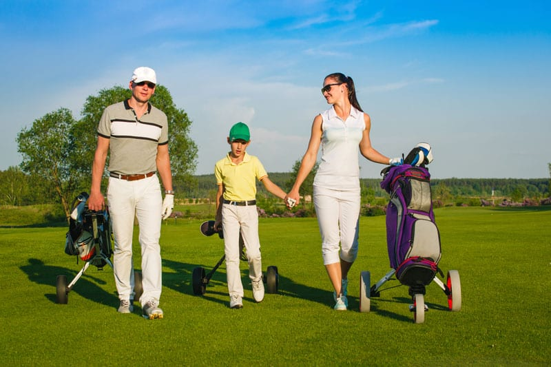 Image of man, woman and child walking down the fairway with golf clubs indicating that golf lessons are for everyone