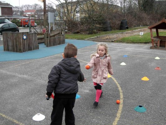 Image #3 of Tri-Golf Session - Little girl passing a ball to a boy.